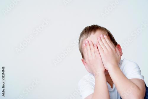 Junge verbirgt Gesicht