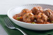 Stewed meatballs with peas, tomato and onion