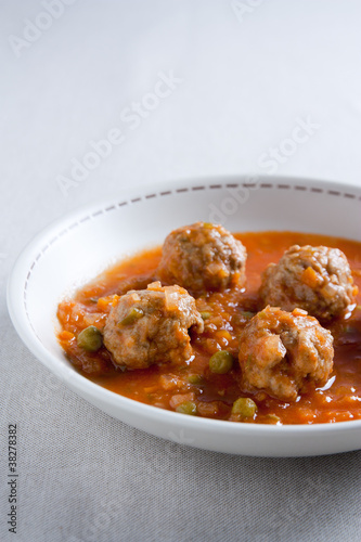 Stewed meatballs with peas, tomato and onion.