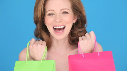 Woman Shopper holding a red and green carrier bag to her chest