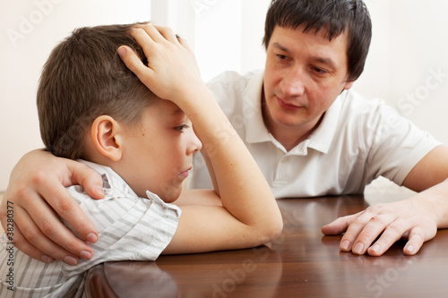 Father comforts a sad child