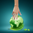 Women hand pointing down to the green globe and leaf