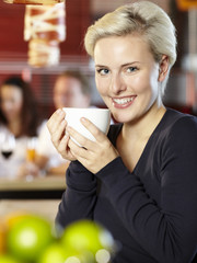 Pretty woman with a cup of coffee sitting at the bar