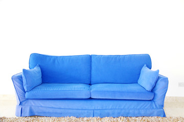 blue double sofa on a blank wall