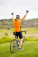 cheerful senior cyclist on top of the mountain