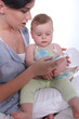 Mother resting baby on knee whilst looking at mobile telephone