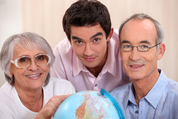 Grown-up family looking at a globe