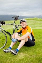 happy senior cyclist resting on grass