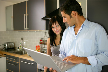 Couple stood in kitchen with laptop