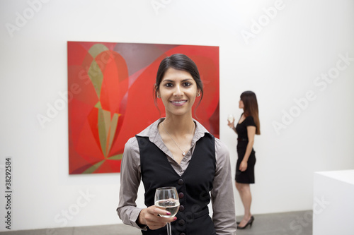 Portrait of young woman in front of painting in museum.