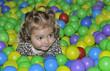 Pequeña jugando entre bolas de colores.