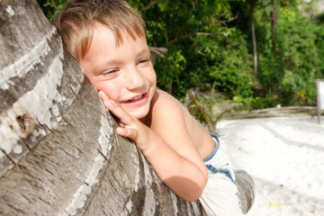 young smiling boy sitting on palm tree