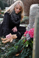 Frau trauert an Kindergrab
