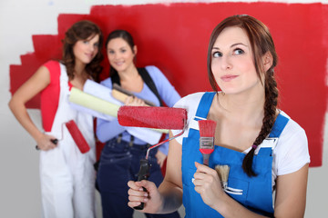 Three female friends painting wall