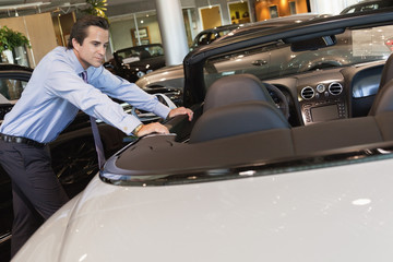Car salesperson leaning on car