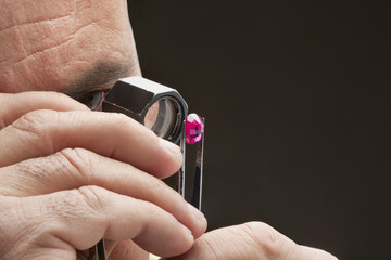 Cropped image of jeweler examining jewel over black background