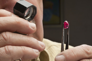 Close up of male jeweler looking at gemstone