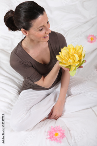 woman sitting cross-legged with water lily