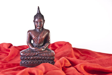 Wooden Buddha statue on Red Fabric