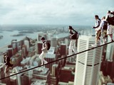 Climbers on a rope with cityscape