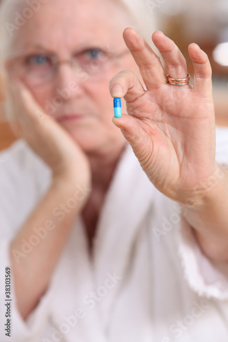 Elderly woman with a pill