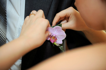 Pinning a boutonniere at wedding party