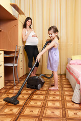 The girl vacuums a floor