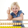 Blonde little girl learning with an abacus shows thumb up