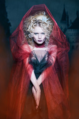 glamorous blonde girl in a maroon cape with stunned hairdo. fair
