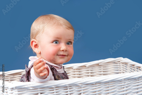 Portrait of toddler sitting in basket