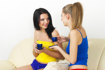 Two young beautiful girls drinking tea and talking