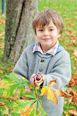 Kind mit Kastanien in der Hand
