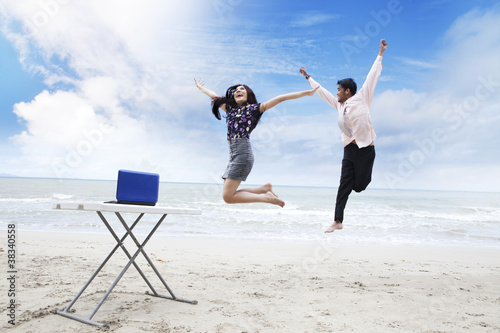 Happy business team on beach