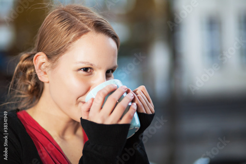 Pretty young woman with cup of chocomilk