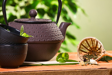 Teapot with cup and fresh mint leaves