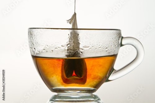 Teabag in a cup filled with hot water isolated on white backgrou