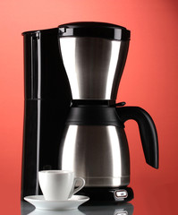 Coffee maker with white cup on red background