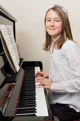 Happy young girl playing the piano
