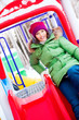 Portrait of young pretty playful woman riding down at playground
