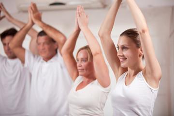 Happy group of people practising yoga