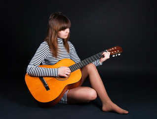 girl with a guitar on a black background