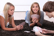 Three teenagers sat playing a card game