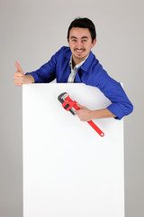Man with a monkey wrench and a blank poster