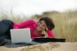 Woman using her laptop at the beach
