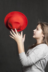 Girl is throwig a red hat
