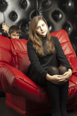 Young girl on a red leather sofa. Angry boy is coming fight