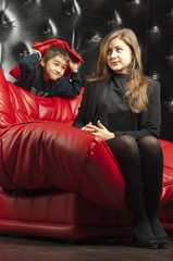Young girl on a red leather sofa