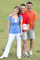 three friends posing with a football