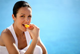 Woman kneeling by swimming pool eating fruit