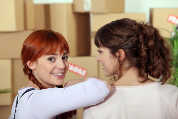 two girlfriends moving into a new apartment